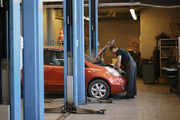 車サービスの専門の自動車整備士は、車、エンジン、エンジン、キャブレターをチェックします。コンセプト: 機械の修理、故障診断、修理専門家、技術メンテナンス、オンボードコンピューター。