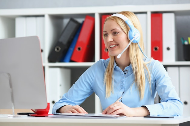 Specialist call center looking at computer monitor and talking to customer