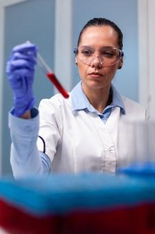 Specialist chemist analyzing blood test tube working at biochemistry experiment