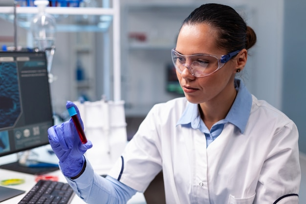 Specialist chemist looking at medical vacutainer with blood analyzing microbiology clinical expertise