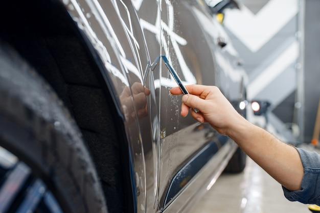 スペシャリストが車の表面の保護フィルムをカットします。