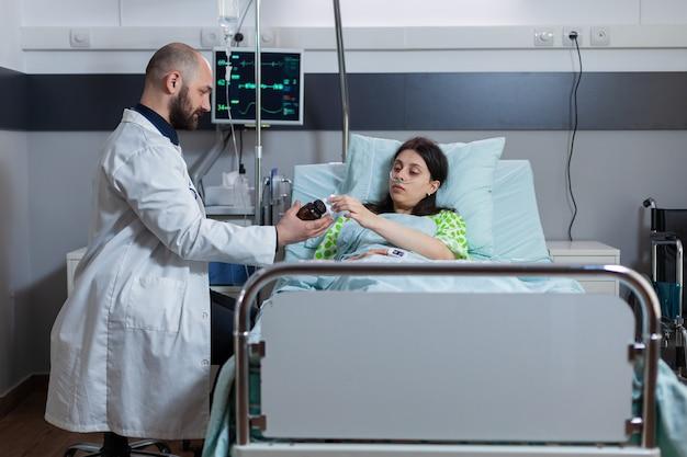 Врач-специалист, проверяющий больную женщину во время медицинского приема в больничной палате, медик ди ...