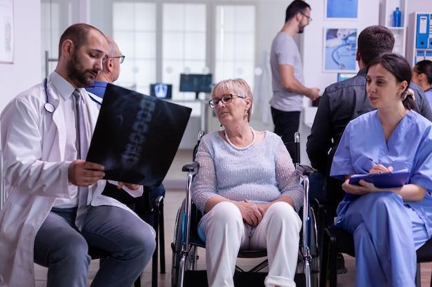간호사에게 진단을 설명하는 환자 엑스레이를 보고 있는 전문 의사