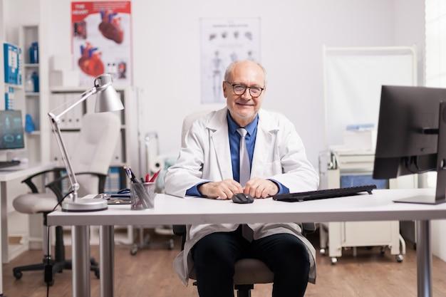 病院のキャビネットで白衣を着た専門医。メディック笑顔。