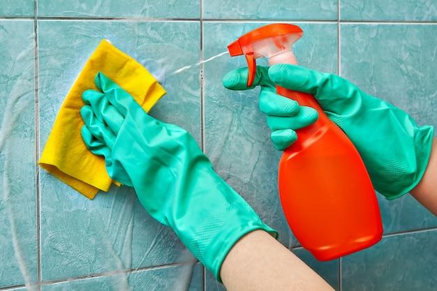 녹색 보호 고무 장갑의 청소 서비스 전문가가 노란색 천과 청소용 폼을 사용하여 샤워시 타일을 닦습니다.