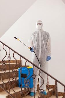 Specialist in hazmat suit spreading antibacterial in office building.