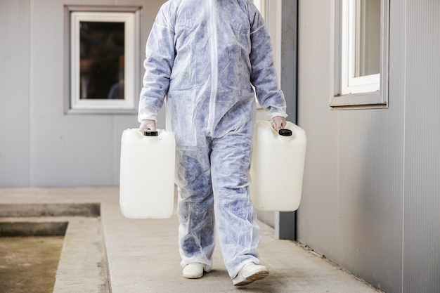 Specialist in hazmat suits preparing for cleaning and disinfecting coronavirus cells epidemic, world pandemic health risk.