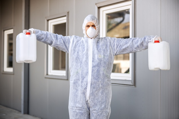Specialist in hazmat suits preparing for cleaning and disinfecting coronavirus cells epidemic