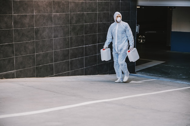 Specialist in hazmat suits preparing for cleaning and disinfecting covid-19 cells epidemic, world pandemic health risk.