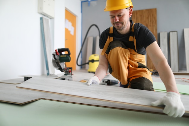 Specialist hold laminate in his handand put it on floor.