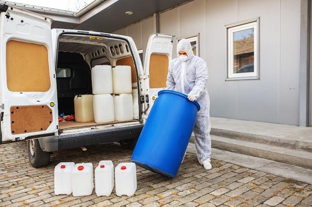 コロナウイルス細胞の流行の洗浄と消毒の準備をする防護服のスペシャリスト