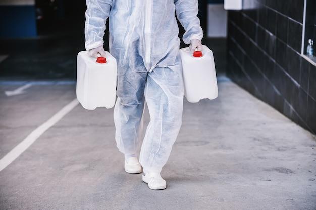 Специалист по защитным костюмам, готовящимся к очистке и дезинфекции эпидемии клеток covid-19, мирового риска для здоровья пандемии.