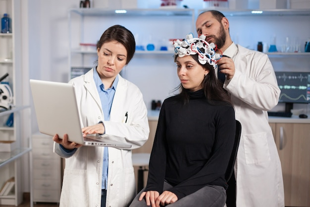 Specialist neurologist doctor taking notes on laptop asking patient's symptoms adjusting high tech eeg headset. doctor researcher controlling eeg headset analyzing brain functions and health status.