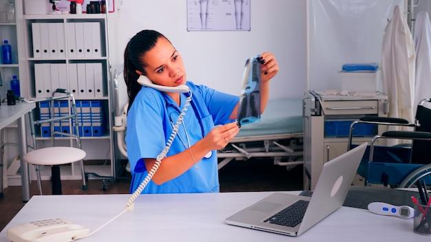 遠隔医療の議論中にそれを保持している患者のx線撮影を分析する専門の放射線科医。医療医師、電話通信、遠隔相談を支援する医師助手