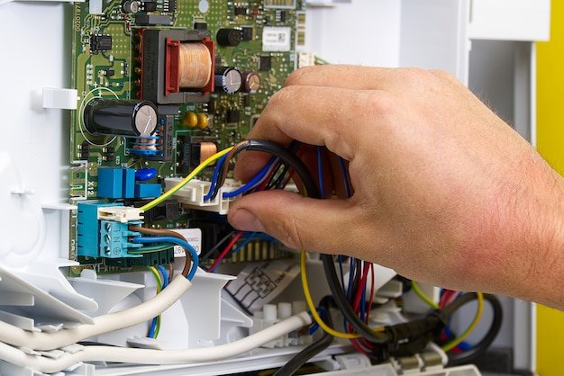 Specialist repairs the electronics of a gas boiler in a private house