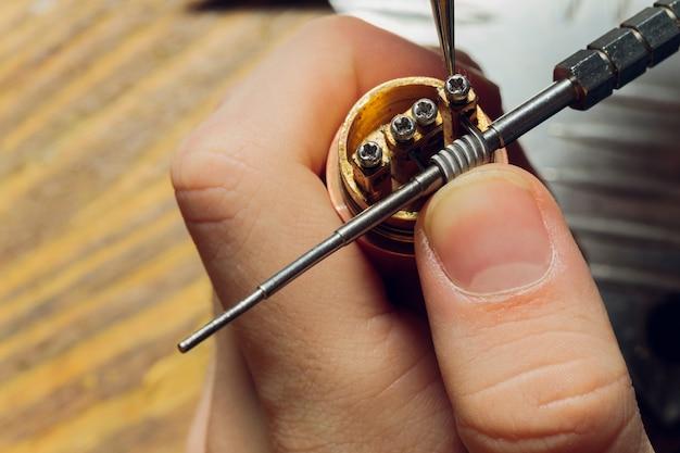 Специалист заменяет пружину для курения вейпа. профессиональный уход за электронной сигаретой в магазине