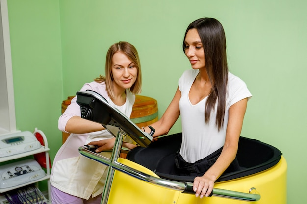 Specialist in spa salon and woman during vacuum training