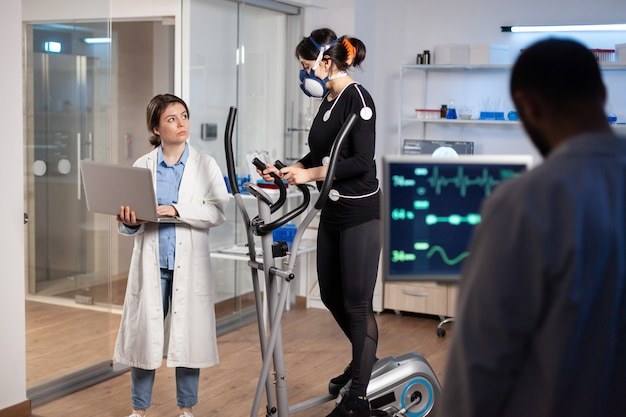 Specialist sport researcher monitoring heart rate on athlete while woman with mask running on cross trainer talking with medical doctor. physician using laptop controling ekg data in modern laboratory