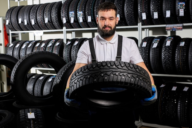 Specialist tire fitting in car service, auto mechanic checks tire and rubber tread for safety, concept: repair of machines, fault diagnosis, repair specialist, technical maintenance. car service shop