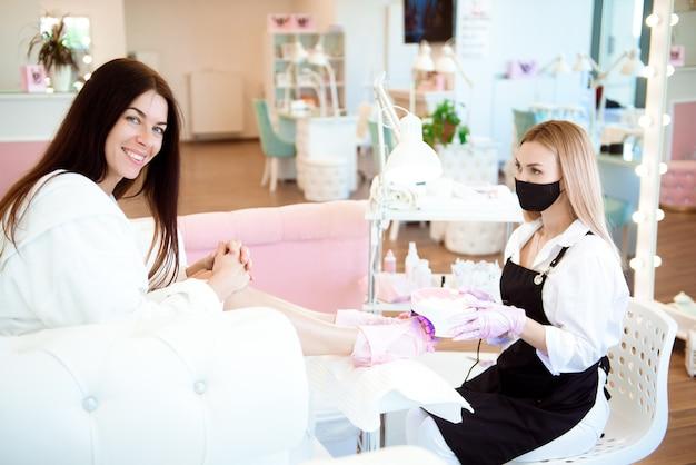 Специалист с клиентом в салоне красоты. профессиональный салон красоты. педикюр, концепция маникюра. удобное кресло.