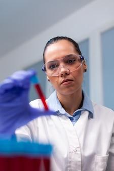 Dna 감염 전문 지식을 분석하는 혈액 의료 vacutainer를 들고 전문 여자 의사