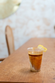Specialty coffee menu called 'dirty coffee' . cold milk in the bottom with hot espresso shot on top with lemon