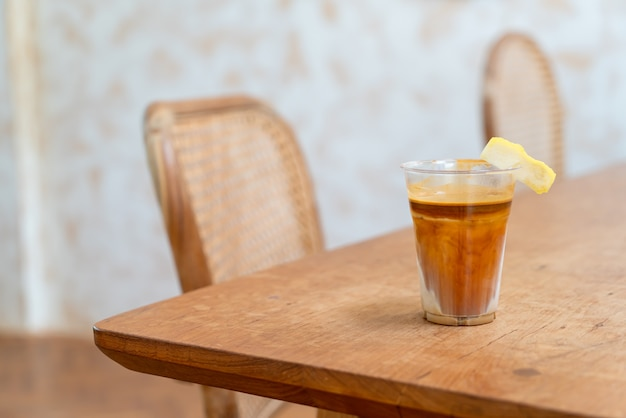 Фирменное кофейное меню под названием «грязный кофе». холодное молоко внизу с рюмкой горячего эспрессо сверху с лимоном