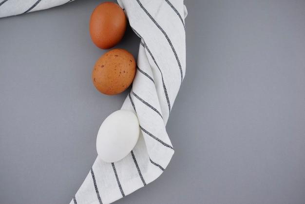 斑点のある茶色と白の卵フラットは、しわくちゃのティータオルナプキンの背景に有機的なスタイリングを置きます