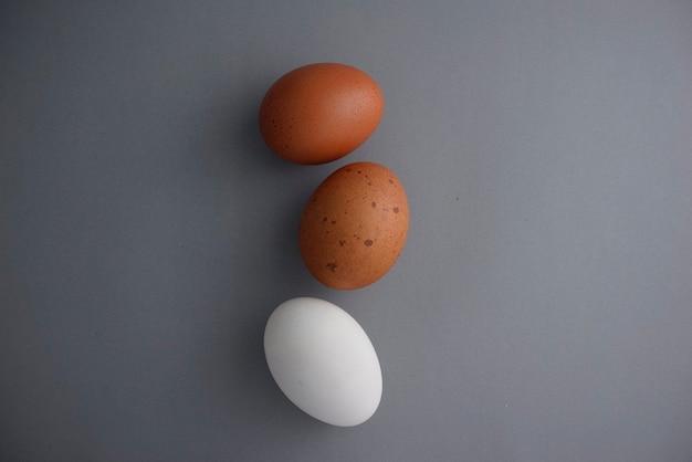 얼룩덜룩 한 갈색과 흰색 계란은 회색 질감 추상적 인 배경에 유기적인 스타일을 평평하게 놓습니다.