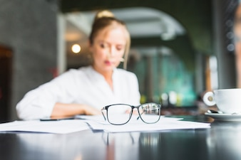 Spectacles and document in front of businesswoman sitting in caf�