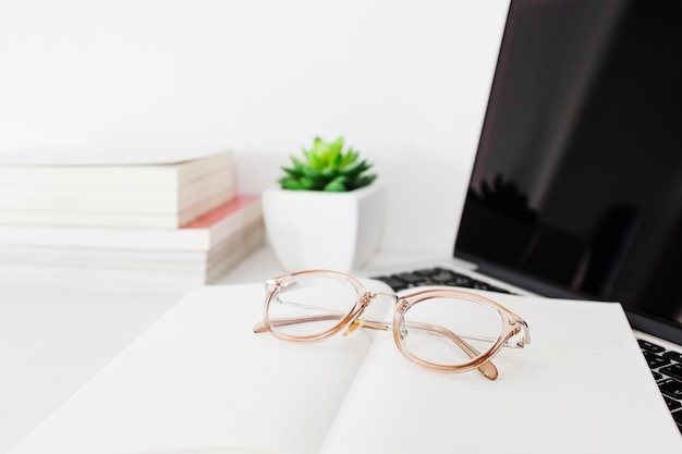Spectacles; notebook and laptop on office desk