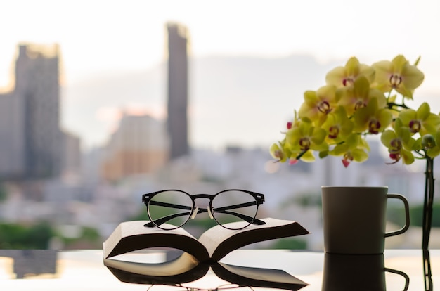 Spectacles put on open book with a cup of coffee phalaenopsis orchid and city