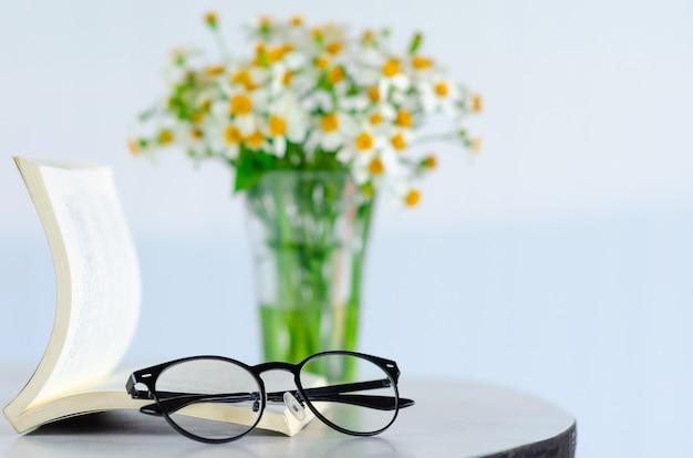Очки ставят на книгу с размытым фоном цветов.
