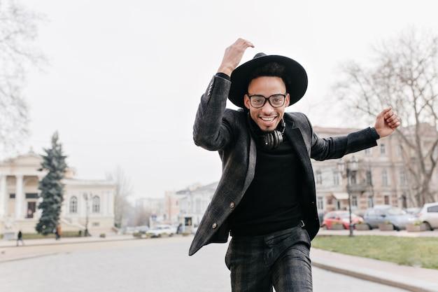 Spettacolare uomo africano con gli occhiali in esecuzione nella sosta di autunno. ritratto all'aperto di un ragazzo nero alla moda in cappello scherzare nella piazza della città