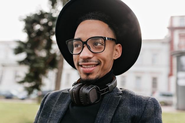 真摯な笑顔でポーズをとる壮大なアフリカ人。メガネとヘッドフォンでかわいい黒人男性モデルの屋外写真。