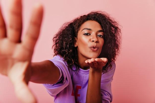 自撮りしながら愛を表現する壮大なアフリカの女性。自分の写真を撮る楽観的な巻き毛の女の子。