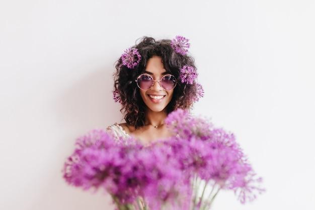 花束を持つ壮大な黒人の女の子。紫色のネギと笑うアフリカの女性の屋内肖像画。