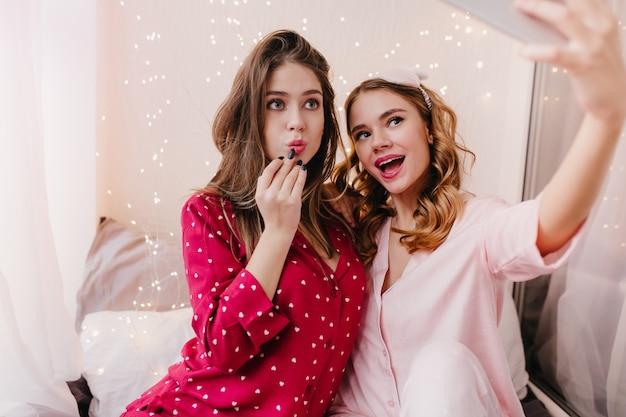 朝の自撮りにスマートフォンを使用している壮大なブロンドの女の子。彼女の部屋で親友とポーズをとる綿のナイトスーツに興味のあるブルネットの女性。