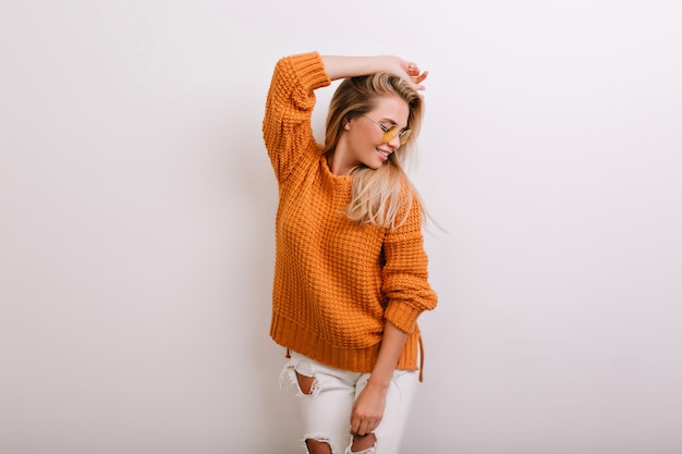 Spectacular blonde woman in warm cardigan posing in front of white wall and looking away