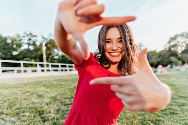 여름 사진 촬영을 즐기는 화려한 갈색 머리 소녀. 주말에 공원에서 장난 치는 행복한 얼굴 표정으로 웅장한 아가씨.