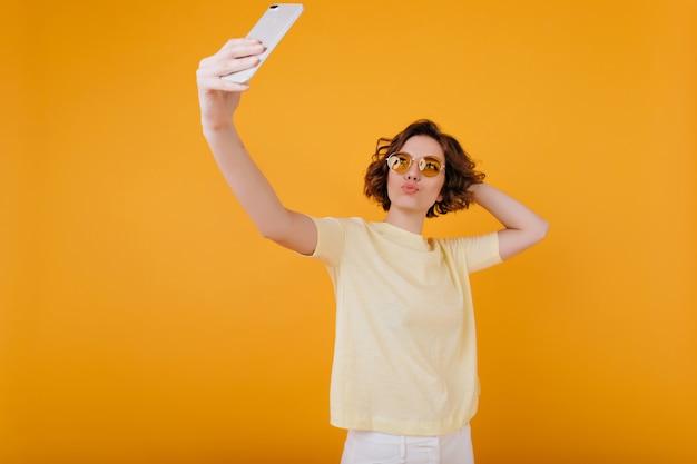 Эффектная кавказская девушка с каштановыми волосами делает селфи в желтой комнате