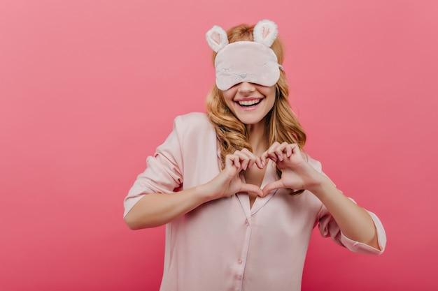眠りにつくアイマスクの壮大な巻き毛の白人女性。ピンクの壁に喜んでポーズをとるポジティブな金髪の女の子の屋内の肖像画。