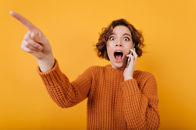 Эффектная темноволосая дама показывает пальцем во время разговора по телефону