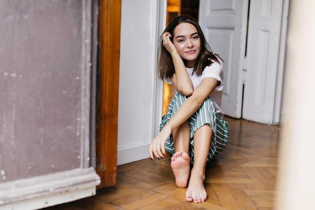 Spettacolare modella femminile in pigiama che si rilassa a casa. foto dell'interno di gioiosa ragazza bruna in posa sul pavimento.