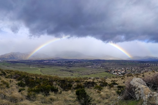 Spectacular full rainbow in the mountains of madrid, sky with dark rain clouds. spain.