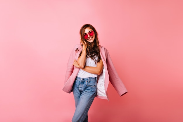 Spectacular ginger girl in denim pants having fun while posing. fashionable white young lady in jacket smiling