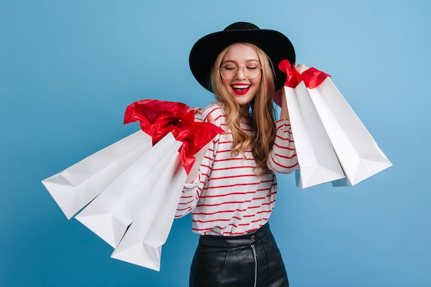 Эффектная девушка в шляпе позирует после покупок. студия сняла прекрасную блондинку, изолированную на синем фоне с сумками.