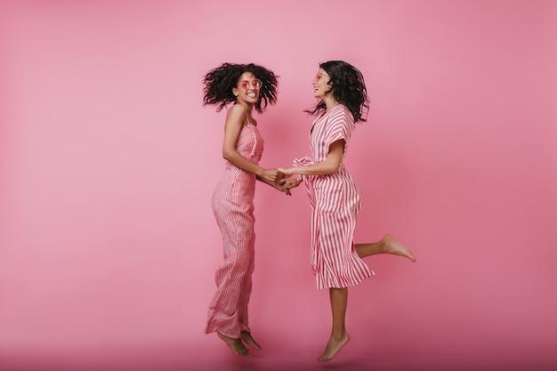 Spettacolare ragazza in abito lungo che balla con la sua amica. tiro al coperto di donne divertenti che tengono le mani e saltano.