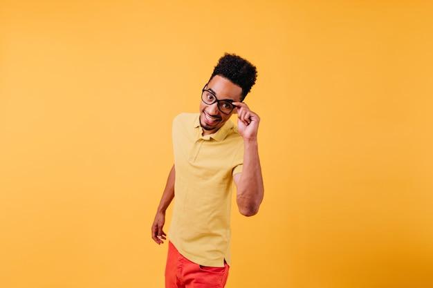 眼鏡のポーズで壮大なインスピレーションを得た男。楽しんでいる興奮したアフリカ人。