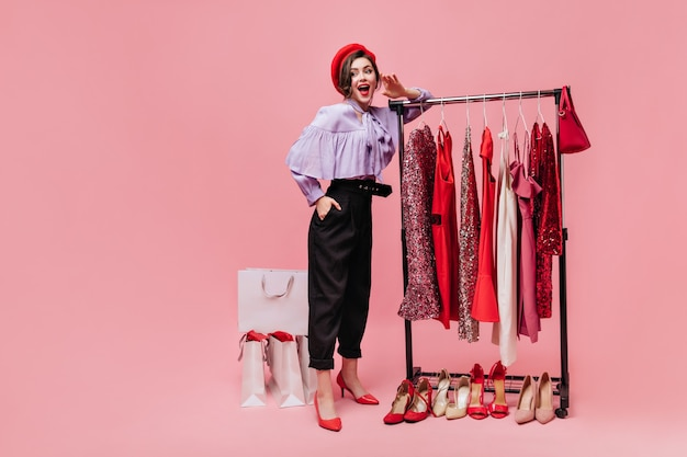 Эффектная дама в черных штанах кокетливо поднимает ногу и держит сумку на розовом фоне с пакетами после покупок.